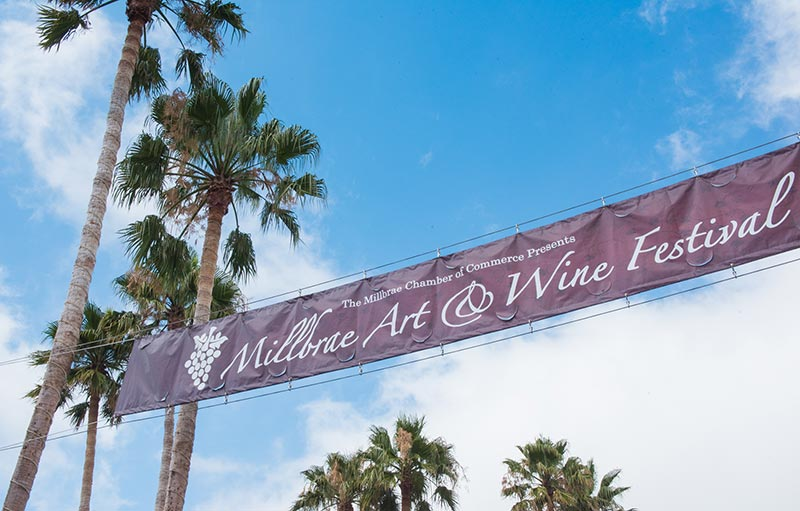 Millbrae festival banner with blue sky and palm trees